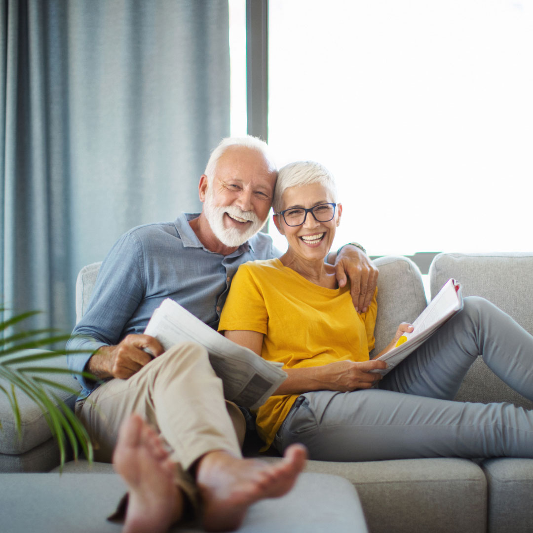 A senior couple sitting on a couch together reading the paper